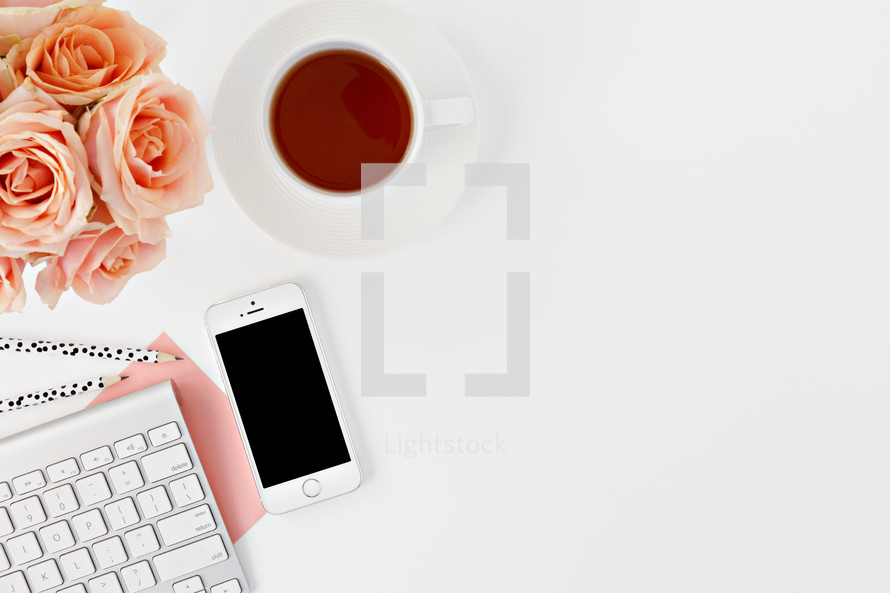 phone, computer keyboard, pencils, tea cup, and peach roses on a desk