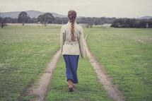 a girl walking on a worn path