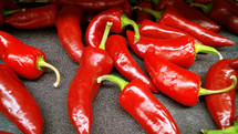 A group of red shiny peppers draw the eye and reflect light in the produce stand to attract the eye and show it is good to eat. Spicy, hot food ideal for the summer time or to add to barbecues, tacos or salads.