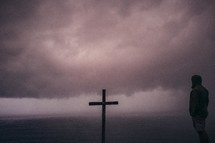 Wooden cross and a man on the ocean water, covered by low-lying storm clouds.