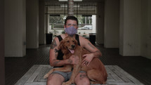 person with tattoos with their dog in a face mask
