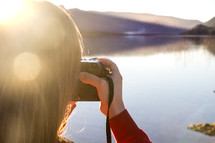 a girl taking a picture with a camera by a lake