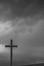 Wooden cross under a stormy sky at the ocean.