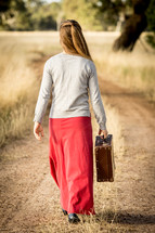 Girl with Suitcase Walking down road