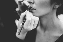 woman putting on lip liner