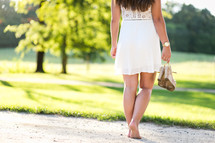 a teen girl walking carrying her shoes