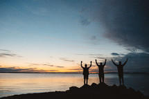 silhouettes of men with raised hands standing by a lake at sunset