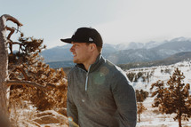 a man in a ball cap standing outdoors in snow