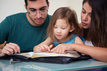 Family Studying Bible With Child