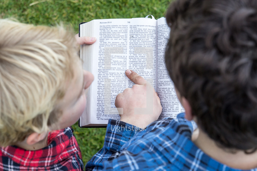 a father reading a Bible to his son