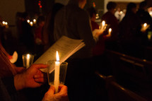 people in a congregation at a Christmas Eve candlelight service