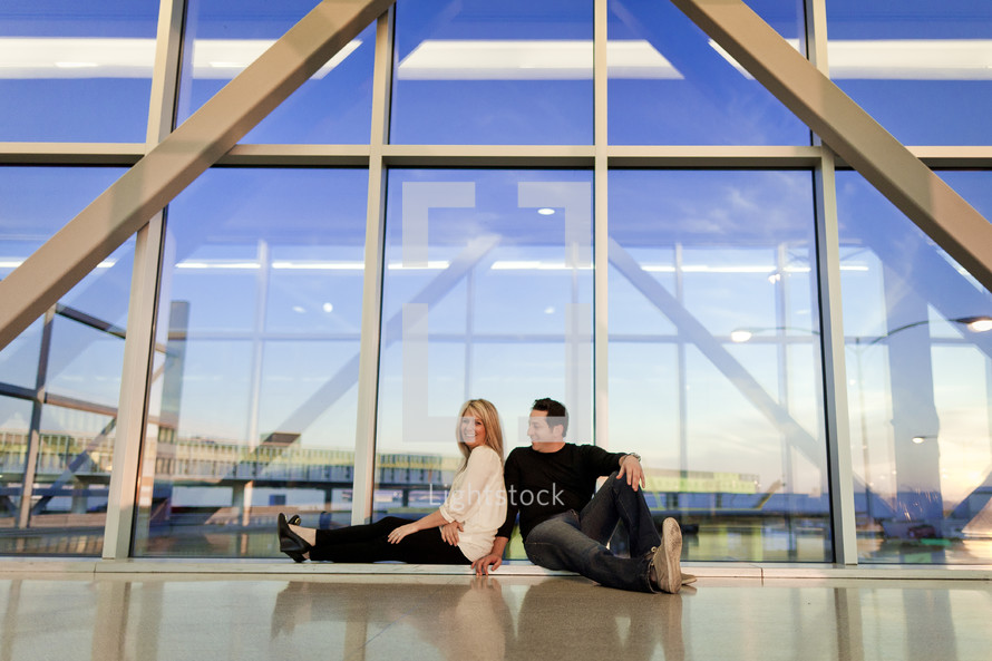 couple sitting on the floor of a city building