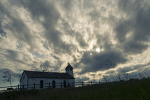 Small country church under dark cloudy sky