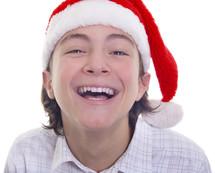 a smiling teenage boy in a Santa hat