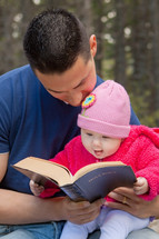 Father and infant daughter reading the Bible outdoors.