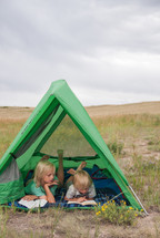 children reading Bibles in a tent