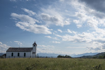 Small white country church on a sunny day, mountains in the background