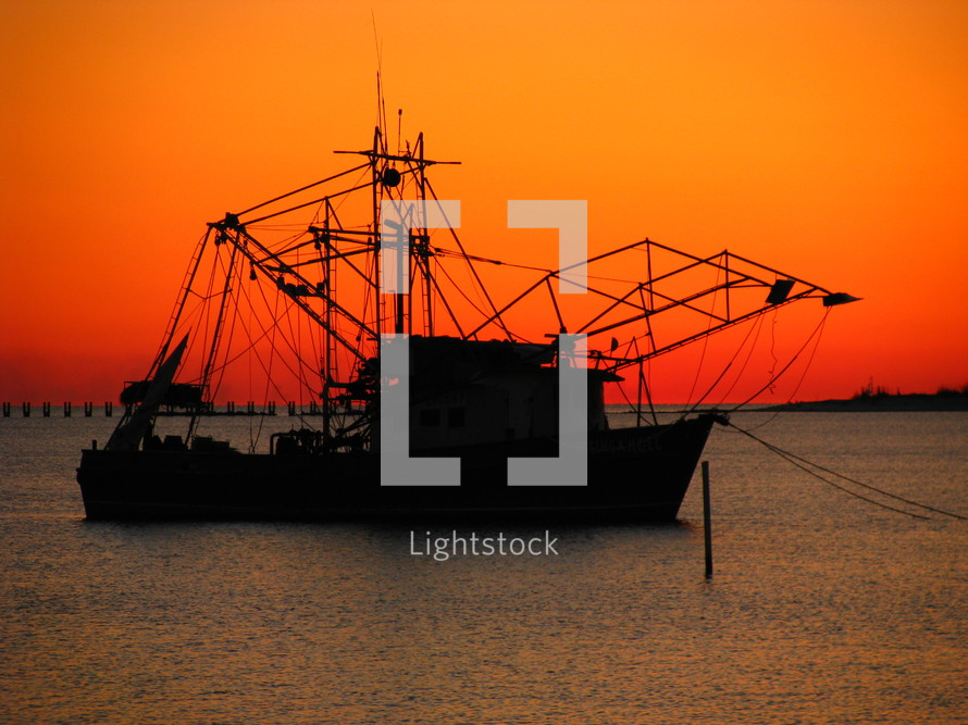 Silhouette of a fishing boat against a beautiful sunset.