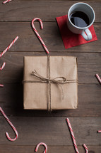 wrapped gift, candy canes, wood floor, brown paper, coffee, mug, red napkin, wood table, Christmas