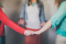 Mother and daughters holding hands in a prayer circle.