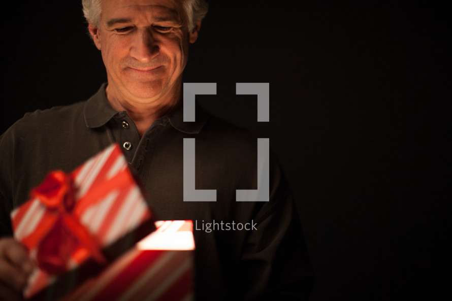 A man looks into a box - An illuminated gift - the gift of salvation through Jesus Christ