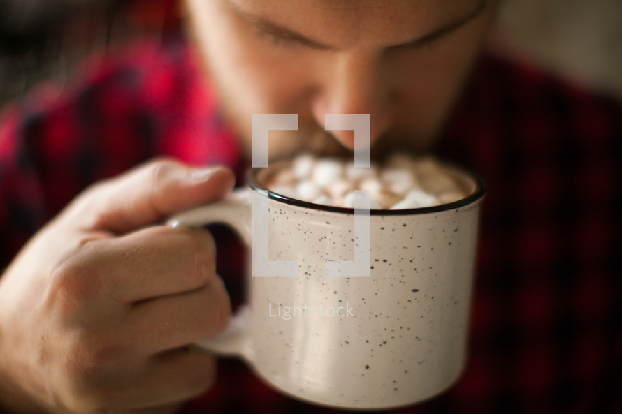 man in a plaid shirt drinking hot cocoa