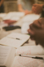 praying hands over Bibles and journals at a Bible study