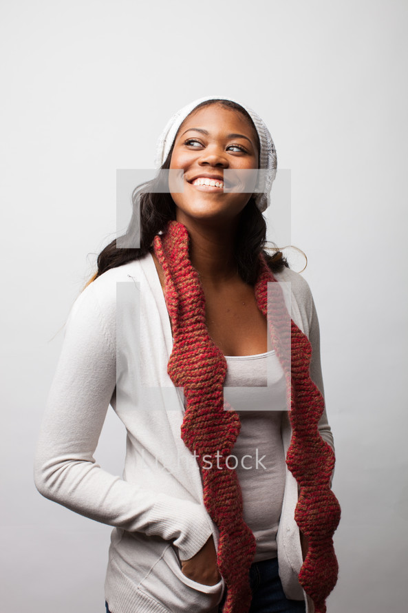 A happy woman wearing a scarf and hat.