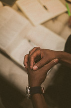 praying hands over a Bible and journal