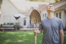 man holding a shovel and looking up to God