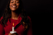 A woman holding a candle.