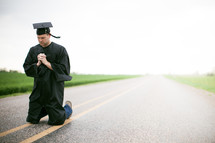 Graduate kneeling in the middle of the road in prayer.