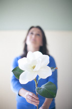 woman holding a magnolia flower looking up to God
