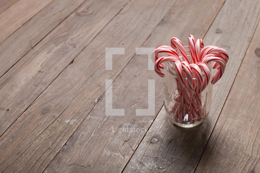 mason jar, glass, candy canes, wood floor