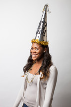 A woman wearing a New Year's party hat.