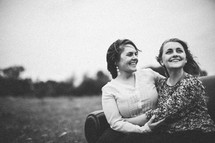 Smiling mother and daughter embracing while sitting on a couch in a field.