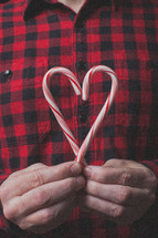 man in a plaid shirt holding a candy cane in the shape of a heart