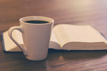 open Bible and coffee mug on a table