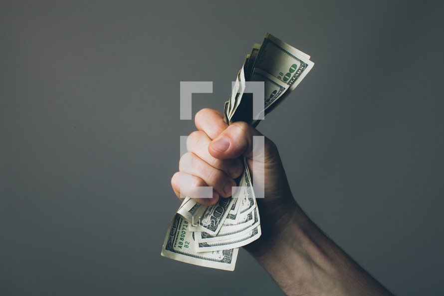 Hand grasping folded stack of paper money.