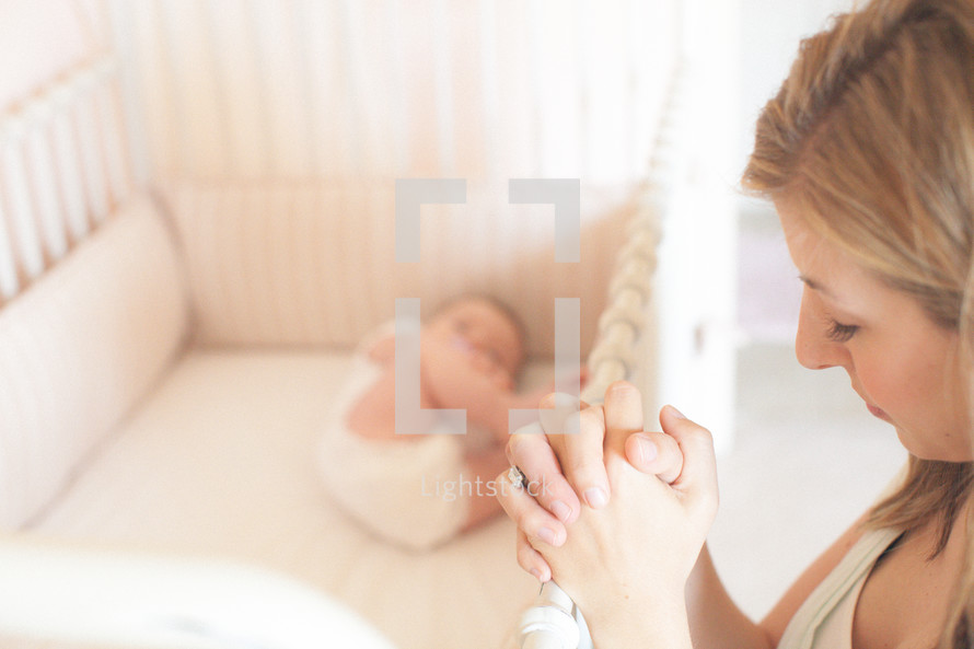 mother praying next to a baby in a crib