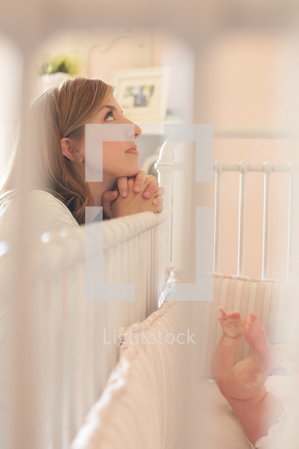 Woman praying over crib with infant.
