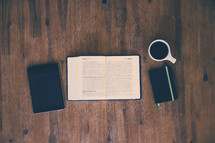 journal, coffee mug, open Bible, and book on a wood floor