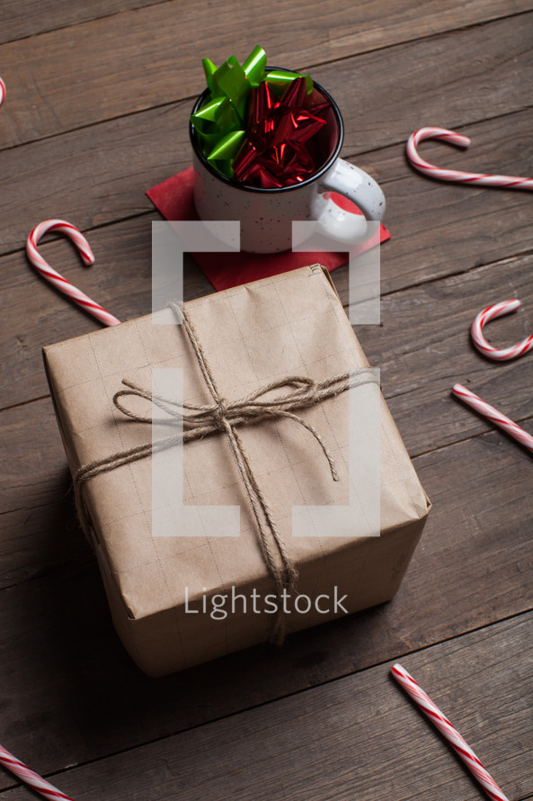 mug with bows, wrapped gift, and candy canes spread out on a wood floor