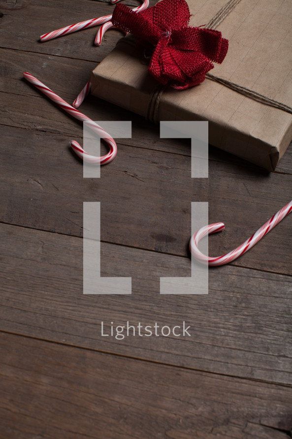 candy canes and wrapped gift on a wood floor