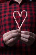 man holding candy canes in the shape of a heart