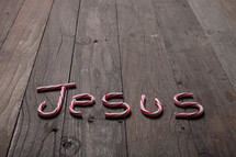 word Jesus out of candy canes on a wood floor