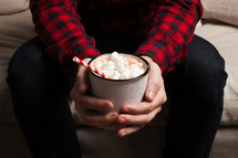 a man in a plaid shirt holding a mug of hot cocoa