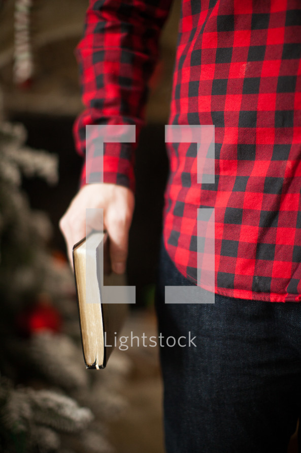 torso of a man in a plaid shirt holding a Bible at his side
