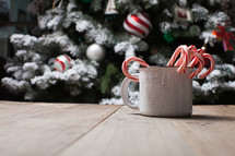 decorated flocked Christmas tree and candy canes in a mug