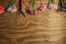 Drying flowers laying on a panel of wood.